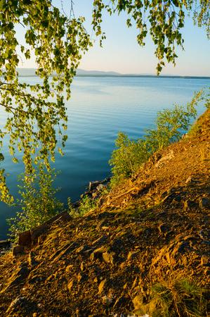 Summer sunset landscape - summer lake, rippled water surface lit by sunset summer light. Summer sunny water scene in soft tones