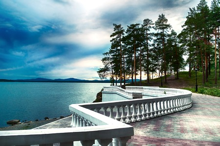 Summer stormy landscape - summer trees and lake under dramatic stormy sky and sculpture fence along the coast. Picturesque summer landscape evening scene Stock fotó