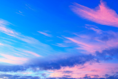 Sunset colorful sky background with pink, purple and blue dramatic colorful clouds. Vast sunset sky landscape