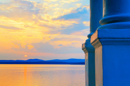Sea landscape. White column on the foreground and sea water surface lit by sunset light. Sea summer nature with mountain range at the horizon Stock fotó