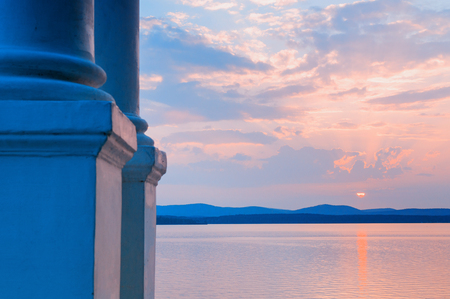 Sea landscape. White column on the foreground and sea water surface lit by sunset light. Sea summer nature scene with mountain range at the horizon
