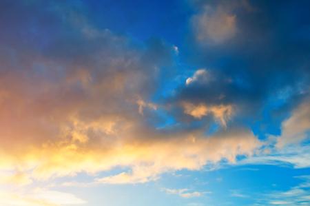 Sunset colorful sky background - pink, orange and blue dramatic colorful clouds lit by evening sunshine. Vast sunset sky landscape Stock fotó