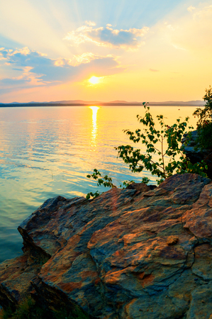 Summer landscape - summer trees at the edge of the stone cliff and lake lit by shining sunset light. Colorful summer landscape evening landscape