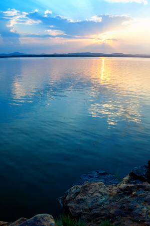 Summer sunset landscape - stone cliff and lake lit by cold evening light. Dramatic summer landscape scene Stock Photo