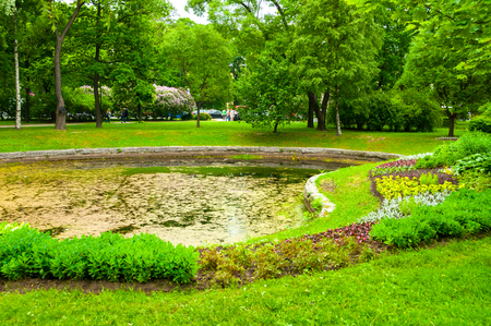 St Petersburg, Russia - June 19, 2015. Landscaping and pond with flowerbeds in the Alexander park - ornamental public park in St Petersburg, Russia Imagens - 124914310