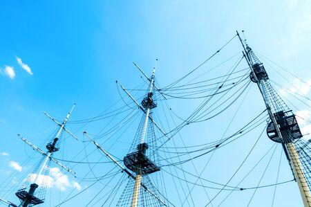 Paisaje de viaje: mástiles de barco con aparejos en el fondo del cielo azul del verano. Concepto de viaje por mar. Primer plano de mástiles de barco contra el cielo Foto de archivo