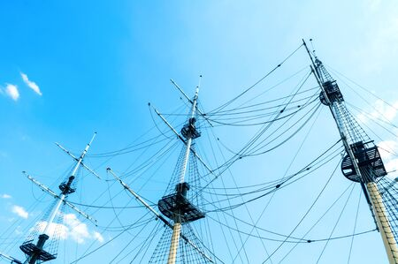 Travel landscape - ship masts with rigging on the background of the blue summer sky. Concept of sea travel. Closeup of ship masts against the sky