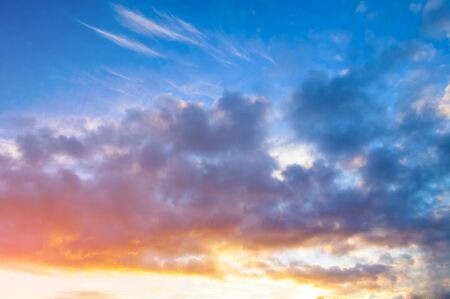 Sunset sky background - pink, orange and blue dramatic colorful clouds lit by evening sunset light. Vast sunset sky landscape scene Banco de Imagens