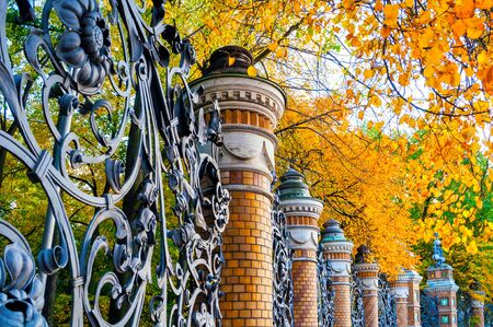 Autumn in St Petersburg. Fence of the Mikhailovsky Garden in St. Petersburg, Russia in autumn day. Autumn architecture view of St Petersburg landmark framed by autumn yellowed trees Banque d'images
