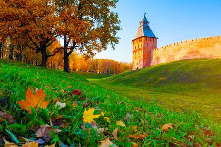 Veliky Novgorod, Russia. Saviour Tower of Veliky Novgorod Kremlin and autumn alley of Kremlin park in sunny day. Focus at the towers