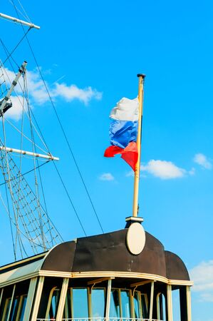 Flag of Russia against blue sky - travel background. Closeup of waving Russian flag on the background of the blue sky, sea travel concept Banco de Imagens