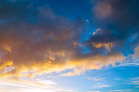 Blue dramatic sunset sky background - picturesque colorful clouds lit by sunlight. Vast sky landscape panoramic scene
