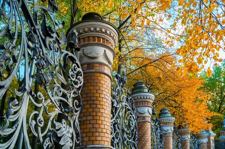 Autumn in St Petersburg - fence of the Mikhailovsky Garden in St Petersburg, Russia in autumn day. Autumn park view of St Petersburg landmark framed by autumn yellowed trees