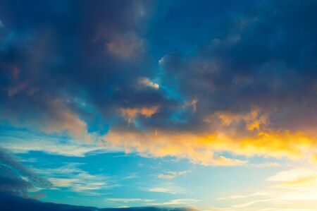 Blue dramatic sunset sky background - picturesque colorful clouds lit by sunlight. Vast sky landscape panoramic scene, sunset evening view 스톡 콘텐츠