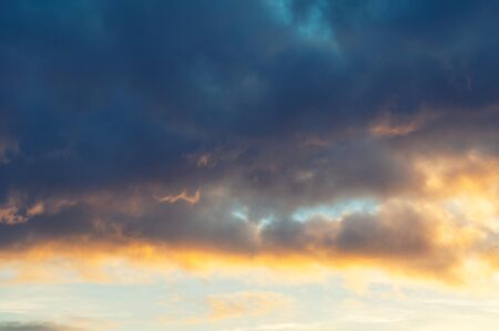 Blue dramatic sunset sky background - picturesque colorful clouds lit by sunlight. Vast sky landscape panoramic scene, sunset evening sky view