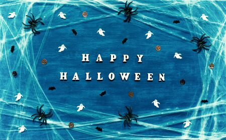 Halloween festive background. Happy Halloween letters with spider web, spiders and Halloween decorations on the dark blue background Stock fotó