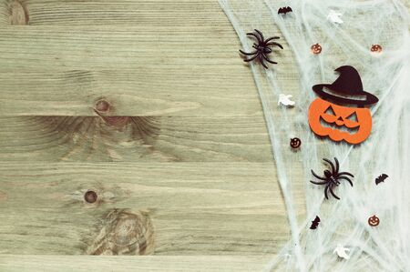 Halloween festive background. Spider web, spiders and smiling jack decorations as symbols of Halloween on the wooden background
