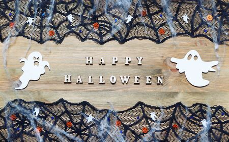 Halloween festive background. Happy Halloween letters and Halloween decorations in form of the ghosts as the symbols of Halloween on the dark wooden background