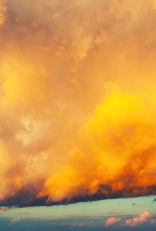 Orange bright dramatic sky background - picturesque colorful clouds lit by sunlight. Vast sky landscape panoramic scene, colorful sky view