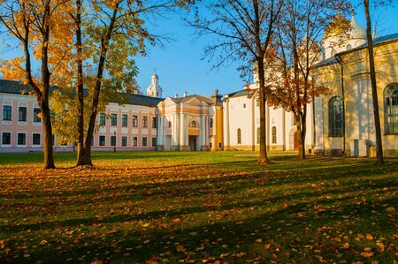 Veliky Novgorod Kremlin park. Clock Tower and St Sophia Cathedral and fallen autumn leaves on the foreground in Novgorod, Russia. Focus at the architecture