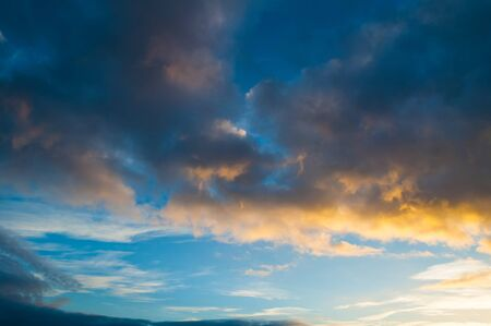 Blue dramatic sunset sky background - picturesque colorful clouds lit by sunlight. Vast sky landscape panoramic scene, sunset evening sunny view Stock fotó