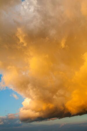Orange dramatic sky background - picturesque colorful clouds lit by sunlight. Vast sky landscape panoramic scene, colorful sky view