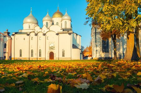 Veliky Novgorod Kremlin park. St Sophia Cathedral and fallen autumn leaves on the foreground in Novgorod, Russia. Focus at the Sophia cathedral. Architecture autumn sunset landscape
