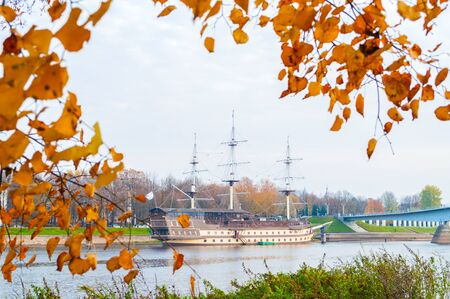 Veliky Novgorod, Russia - October 18, 2018. Frigate Flagship restaurant complex and water area of Volkhov river in Veliky Novgorod, Russia. Autumn cloudy town landscape