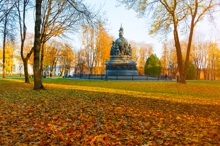 Veliky Novgorod, Russia - October 17, 2018. Bronze monument Millennium of Russia in autumn sunset and people walking in the autumn park in Veliky Novgorod, Russia