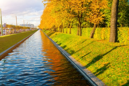 St Petersburg, Russia - October 3, 2016. Autumn landscape of St Petersburg - Swan Canal and autumn park with golden autumn trees in sunny weather. St Petersburg autumn city landscape