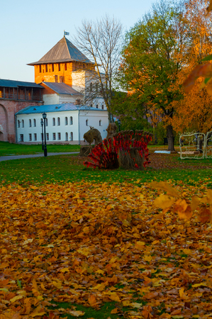 Veliky Novgorod, Russia. Chrysostom or Zlatoust tower of Veliky Novgorod Kremlin and colorful autumn Kremlin park in the autumn evening Sajtókép
