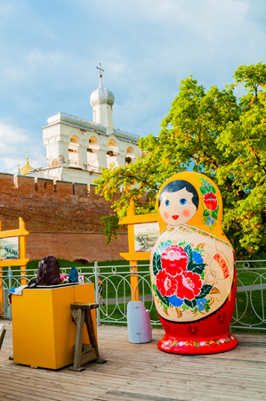 Veliky Novgorod,Russia-August 10, 2019. Belfry of St Sophia cathedral with big colorful Russian matrioshka doll on the foreground in Veliky Novgorod, Russia, travel view