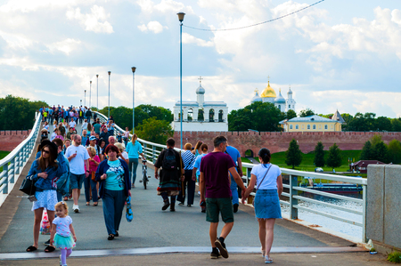 Veliky Novgorod,Russia-August 10, 2019. Novgorod Kremlin and footbridge with people walking across the Volkhov river in summer cloudy day - travel cityscape Sajtókép