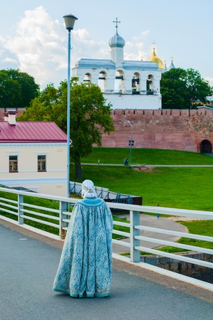 Veliky Novgorod,Russia -August 10, 2019. Woman dressed in Slavic folk clothes is walking on the bridge. Kremlin fortress and belfry of St Sophia Cathedral are on the background