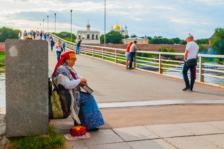 Veliky Novgorod,Russia -August 10, 2019. Woman dressed in Slavic folk clothes is playing the gusli - the oldest East Slavic multi-string plucked instrument. Kremlin fortress on the background Sajtókép