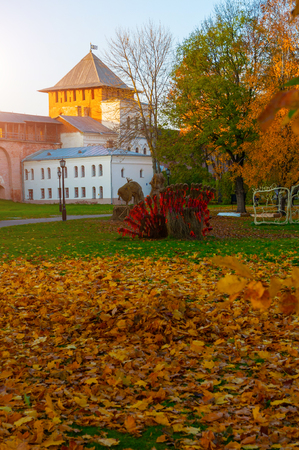 Veliky Novgorod, Russia. Chrysostom or Zlatoust tower of Veliky Novgorod Kremlin and colorful autumn Kremlin park in the autumn sunset