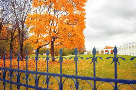 Veliky Novgorod, Russia - autumn landscape scene. Yaroslav Courtyard arcade and metal fence on the foreground in cloudy autumn day