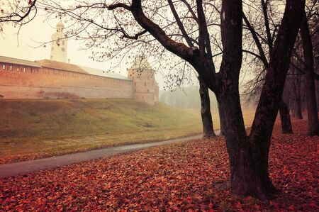 Veliky Novgorod, Russia. Fedor tower and clock tower of Veliky Novgorod Kremlin at autumn foggy day. Focus at the Kremlin towers. Autumn landscape in retro tones