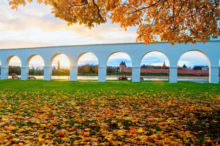 Autumn cityscape of Veliky Novgorod, Russia. Kremlin fortress in the arch spans of Yaroslav courtyard arcade on the bank of the Volkhov river in Veliky Novgorod, Russia - autumn October view