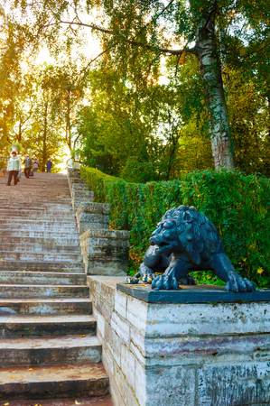 Pavlovsk, St Petersburg, Russia - September 21, 2017. Large stone staircase and sculpture of a black lion on the pedestal in Pavlovsk park, St Petersburg Russia - sunny autumn view