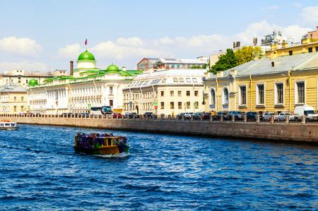 Saint Petersburg, Russia - June 6, 2019. Leningrad Regional Court building and touristic boat floating on the Fontanka River in Saint Petersburg, Russia