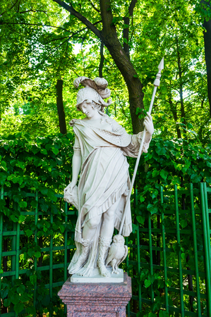 St Petersburg, Russia - June 6, 2019. The goddess Minerva, dressed in armor and resting on a spear, at the feet - an owl as a symbol of wisdom. Summer garden - the most famous garden in St Petersburg