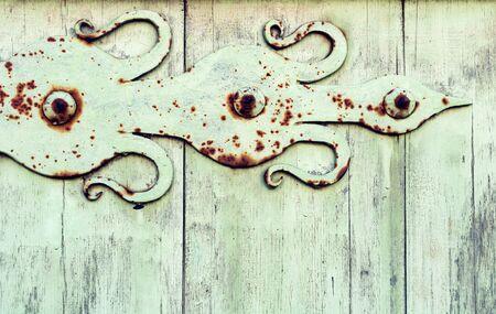 Old wooden light green door with aged metal door hinge. Architectural textured background