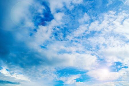 Blue sky background. Picturesque colorful clouds lit by sunlight. Vast sky landscape panoramic scene
