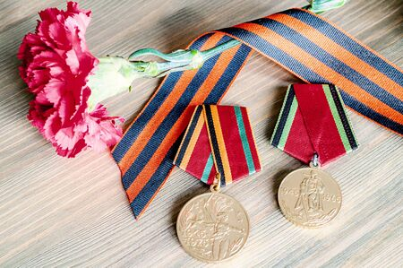 9 May Victory day card with jubilee medals of Great patriotic war, red carnations and George ribbon on the wooden background