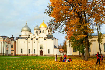 Veliky Novgorod Russia - October 11, 2019. Veliky Novgorod, St Sophia cathedral in the autumn Kremlin park and tourists taking shots in the park in October day in Veliky Novgorod Russia Publikacyjne