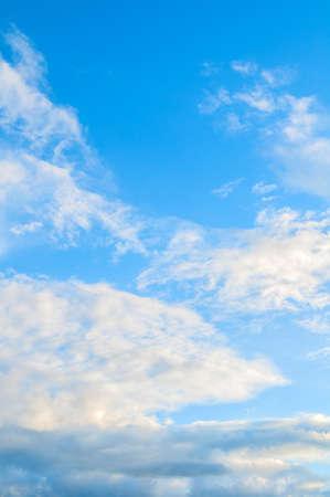 Blue sky background, white dramatic fluffy clouds lit by sunset light. Vast sky landscape scene, blue sky view 免版税图像