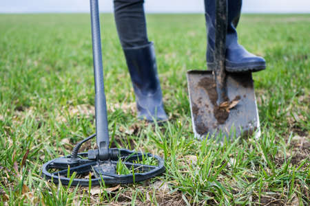 girl archaeologist or metal digger is looking for coins or metal with a metal detector. Search old coins. Scrap metal collection on autumn. Girl in rubber boots with a tool for finding coins.