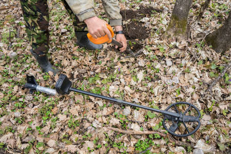metal detector in the forest and a man digging coins. Search for precious old historical coins or metals in grass and earth. Black digger man with metal detector. High quality photo