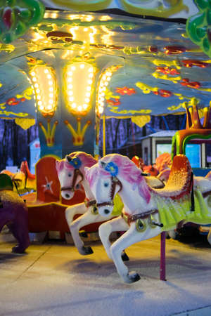 Children's carousel glows beautifully in winter. Attraction for children in the evening with lights. High quality photo